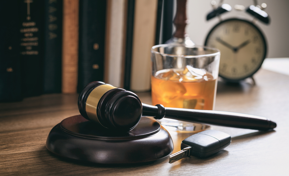 gavel next to car keys and drink