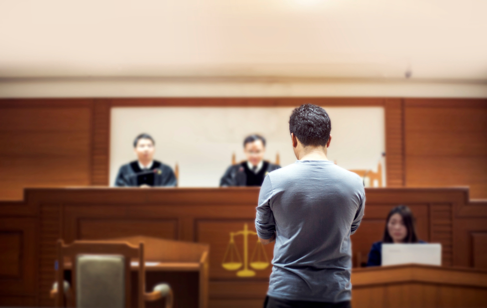 man standing before judges in a court house