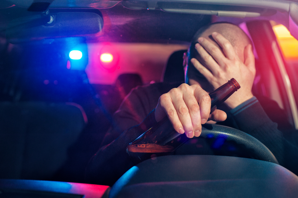 man being pulled over with an open drink in hand