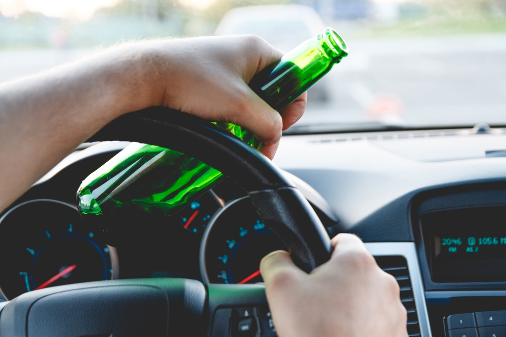 open bottle in hand behind the wheel